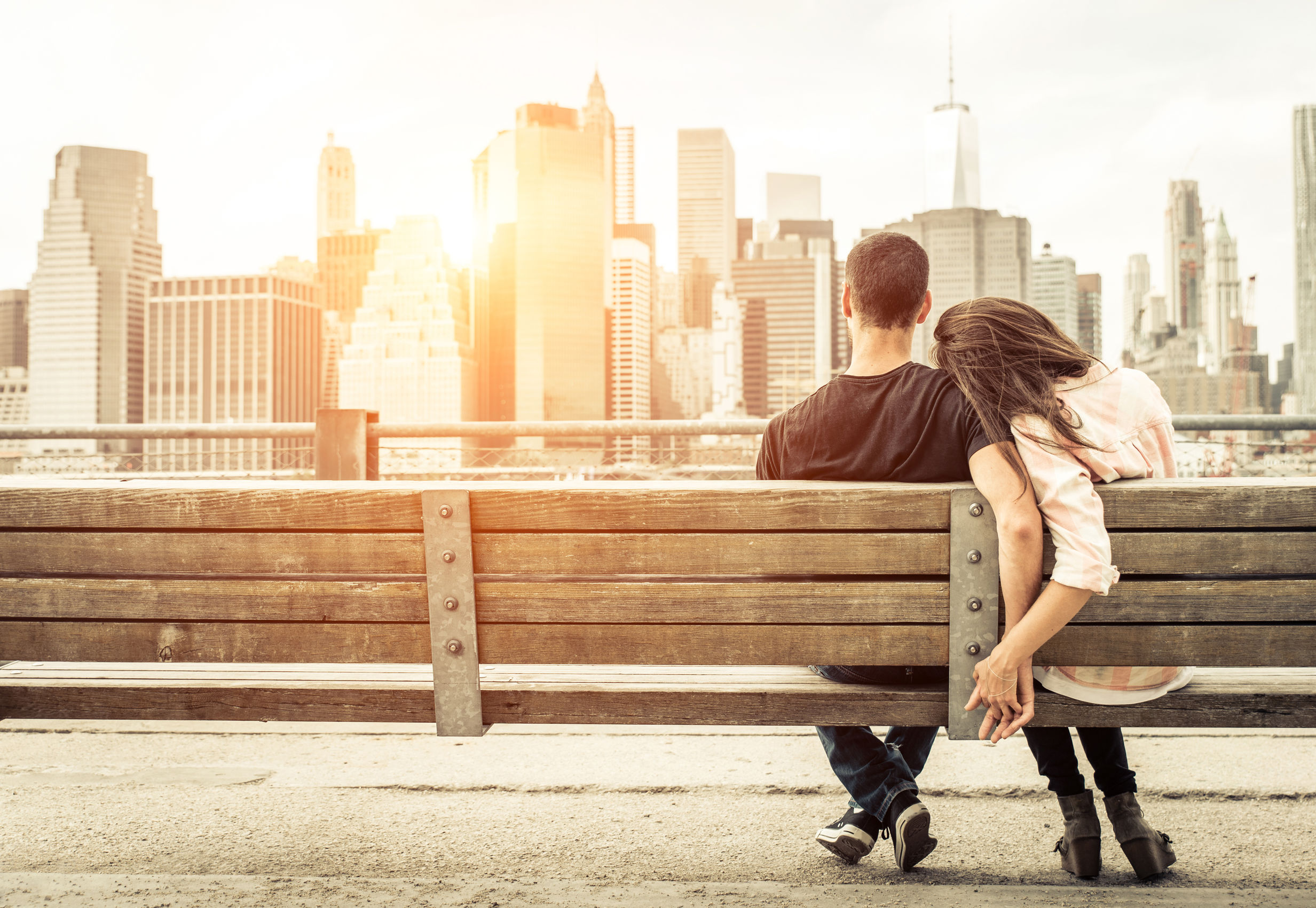 47114383 - couple relaxing on new york bench in front of the skyline at sunset time. concept about love,relationship, and travel