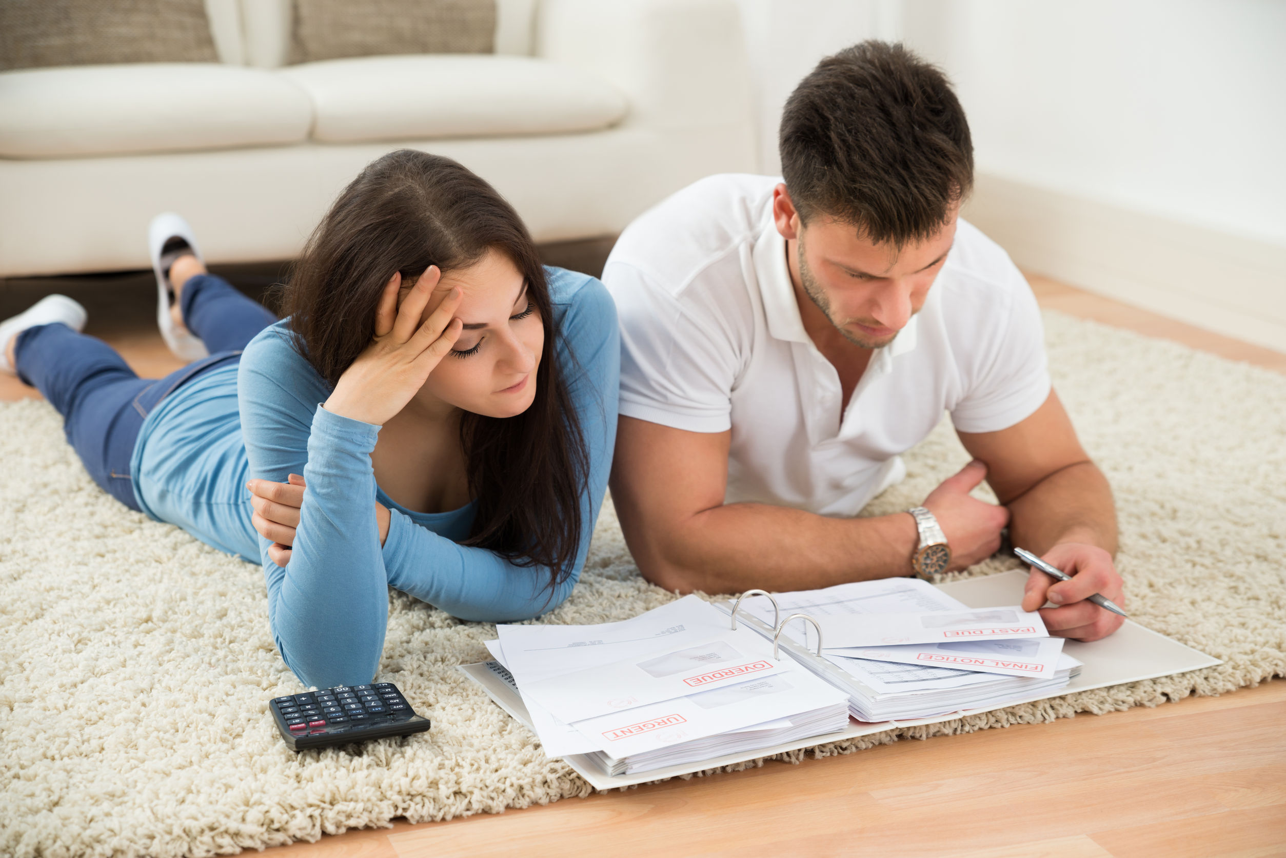 41317954 - worried young couple lying on carpet calculating their bills at home
