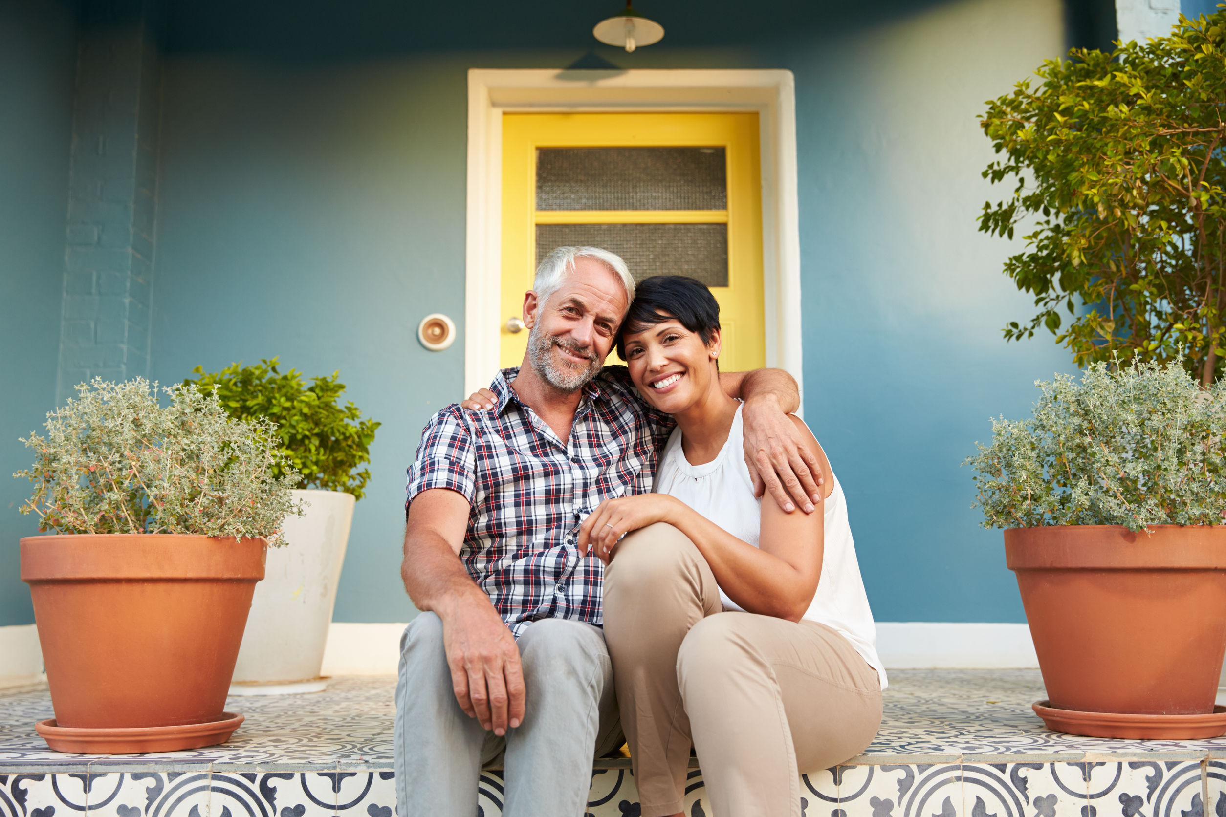 41402318 - mature couple sitting on steps outside house